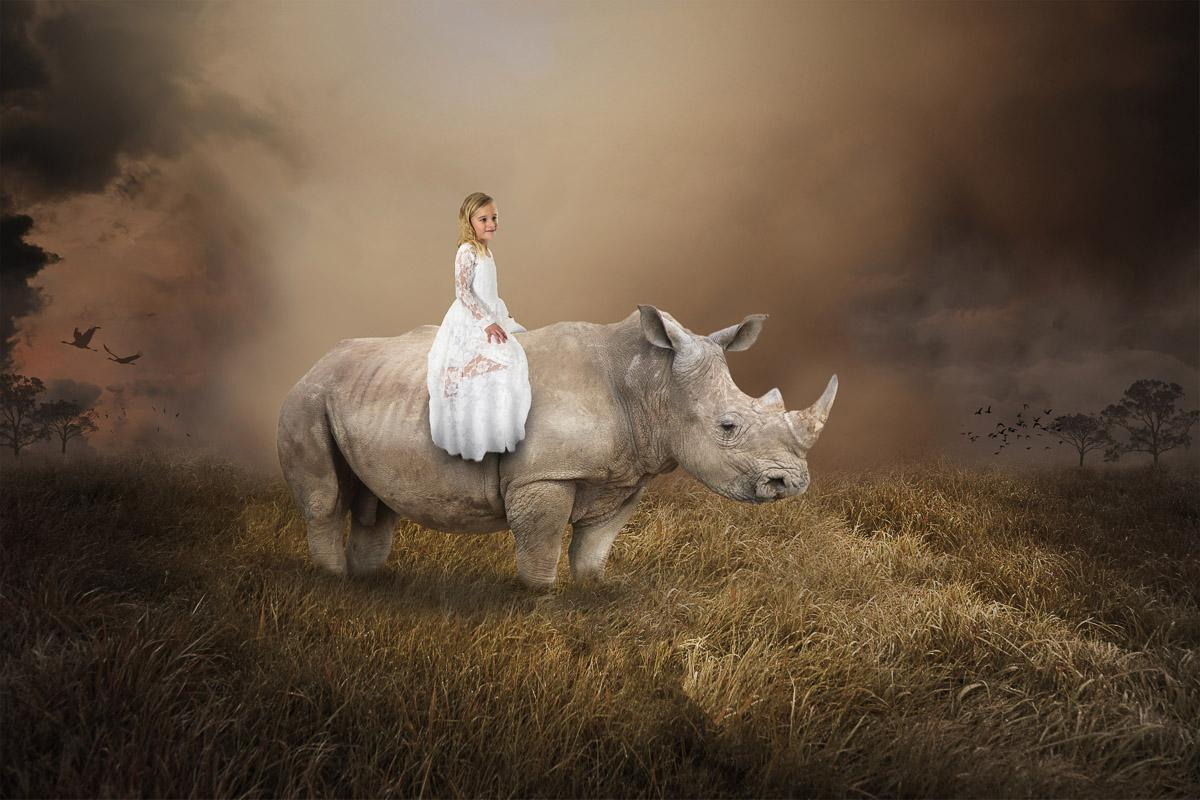 Surreales Mädchen, das Nashorn reitet